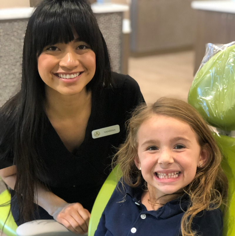 Smiling girl in dental chair with Arcadia staff member